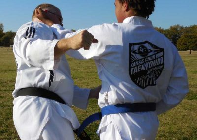 Nathan executes an inward block/strike against Master Mike Swope (Kansas Chun Kuhn Taekwondo)