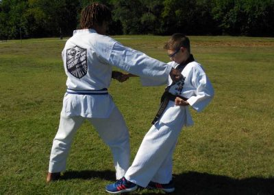 Nathan demonstrates an application from Geicho Sahm Bu (Basic Form 3) of Moo Duk Kwan Taekwondo for horse riding stance side attack punch against Stephen Swope, both of Kansas Chun Kuhn Taekwondo