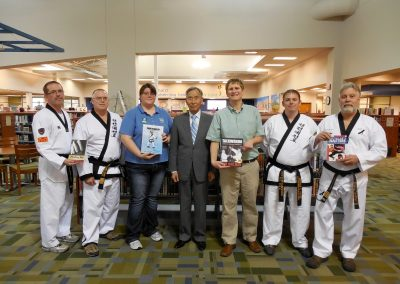 Supreme Master Kim Bok-Man poses with Master Mike Swope; Master Jeramie Swope; the director and staff of the Derby, Kansas Public Library; and instructors of Black Eagle Martial Arts to commemorate the formation of the Martial Arts Book Collection at the library in 2014