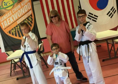 Nicholas received his first Kansas Chun Kuhn Taekwondo dobok in 2017. Also pictured are Nickolas' grandmother, Stephen Swope and Romé Bruce.