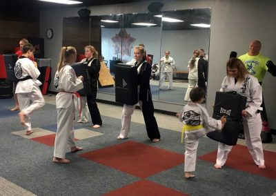 Kansas Chun Kuhn Taekwondo students practice front kicks against body shield