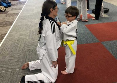 Nickolas practice a self-defense technique with Ms. Tracy Tams