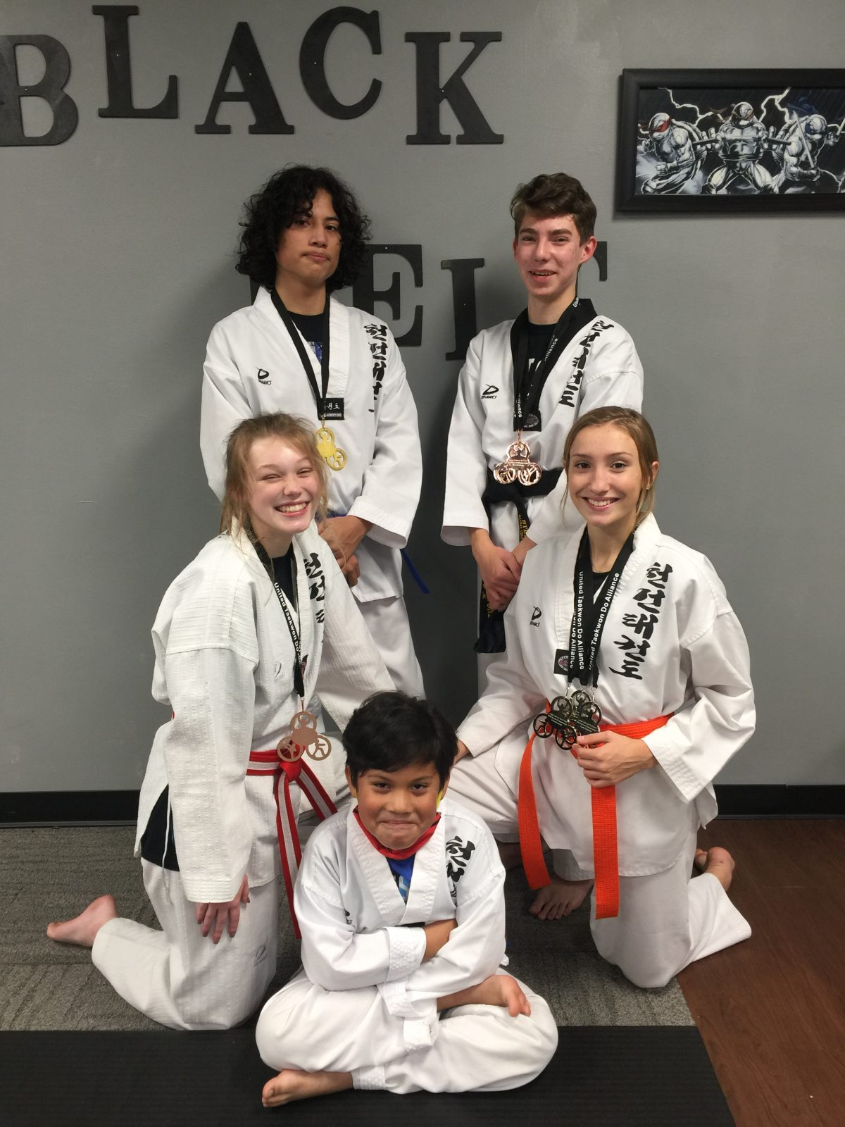 Red Cape Martial Arts competitors pose with their medals from the UTA 2020 National Championships. Front: Sebastian Alvarez; 2nd Row L-R: Romé Bruce, Peyten Cooper; 3rd Row L-R: Santos Alvarez, Stephen Swope.